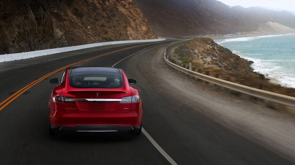 Red Tesla S85 on a California highway near the ocean. A Diminished Value Appraiser in Southern California call 772-359-4300.