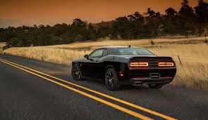 A black Dodge Challenger driving past a field. A Diminished Value Appraiser in Raleigh, North Carolina call 772-359-4300.