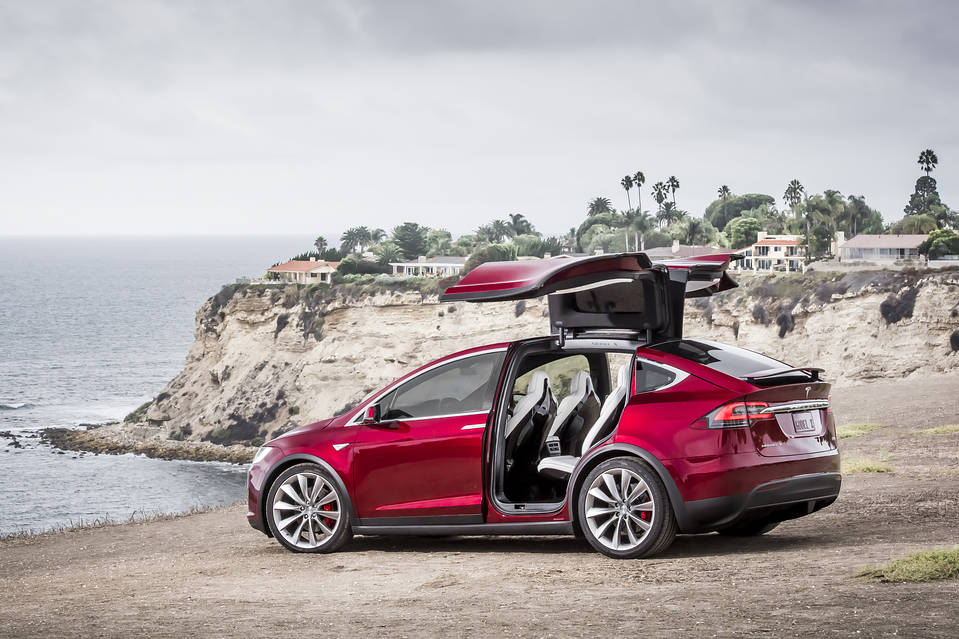 Red Tesla Model 3 on the beach. A Diminished Value Appraiser in California call 772-359-4300.